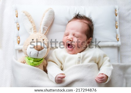 Adorable sleepy newborn baby with a toy bunny yawning in bed - stock photo