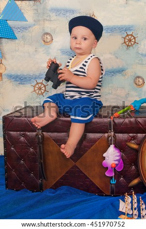 Adorable small child with the field-glass in a suit of the seaman smiling and having fun in studio. Sea style. Dreams of the ship, adventures and travel. Portrait of funny lovely little baby