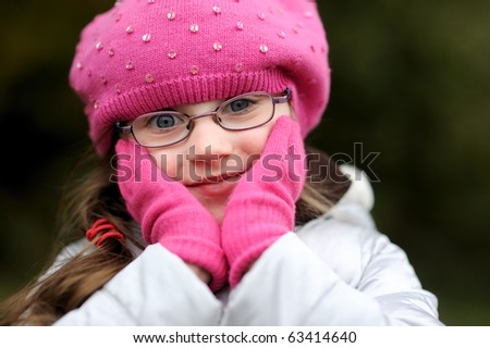 Adorable small girl in bright pink hat with long dark hair and glasses with her hand in gloves near the face - stock photo