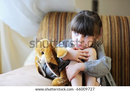 Adorable small girl with dark hair in grey dress hugs her bunny - stock photo