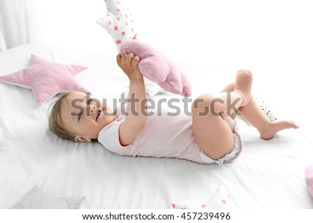 Adorable smiling baby girl on a white sheet