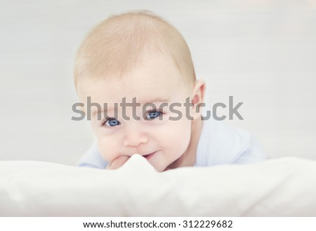 Adorable smiling baby lying in the bed - stock photo