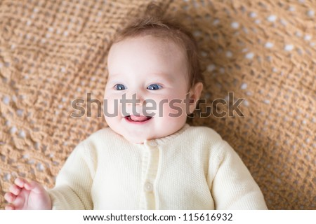 Adorable smiling baby on a warm knitted blanket - stock photo