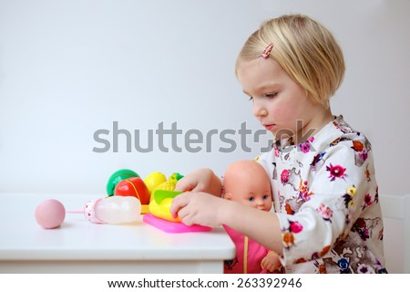 Adorable smiling child, blonde toddler girl wearing beautiful dress, playing at home or kindergarten, feeding her doll with toy bottle, plastic fruits and vegetables sitting at white wooden table - stock photo