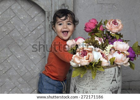 Adorable smiling little boy with flowers by the fireplace - stock photo