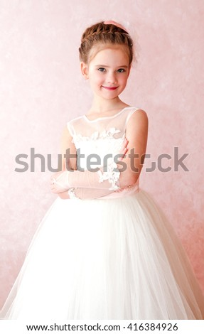 Adorable smiling little girl in white princess dress isolated