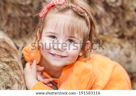 Adorable smiling little girl on the plush sofa - stock photo