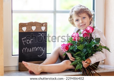 Adorable smiling little kid boy with blooming pink roses in bunch and blackboard, congratulating his mum for mother's day - stock photo