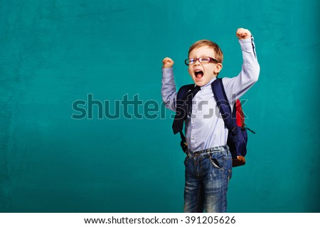 Adorable smiling little kid with big backpack jumping and having fun against blue wall. Looking at camera. School concept. Back to School - stock photo