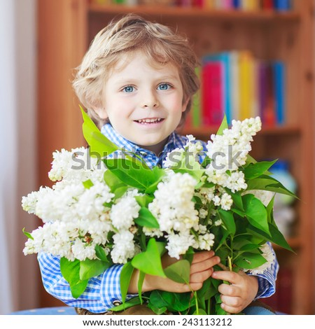 Adorable smiling little toddler boy with blooming white lilac flowers, indoor. Mother's day, father's day or valentine's day concept. Birthday card. - stock photo