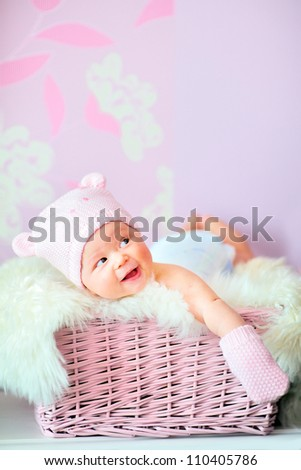 adorable smiling newborn baby girl in pink knitted bear hat and mittens lies at basket