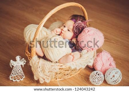 adorable smiling newborn baby girl lies in basket - stock photo