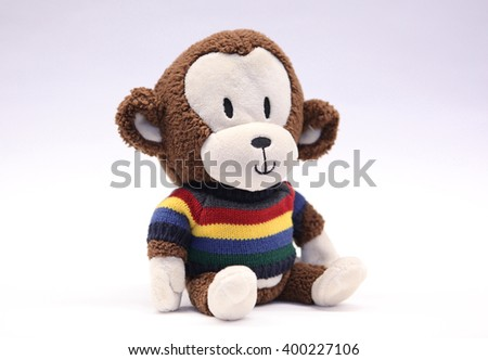 Adorable smiling stuffed sitting monkey toy.  He has a fuzzy brown body with ivory face, hands and feet and is wearing a light and dark blue, green, yellow and red striped sweater. - stock photo