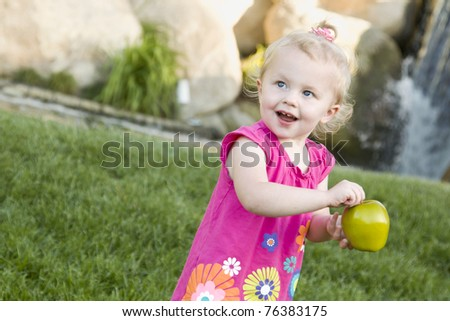 Adorable Smiling Young Girl in The Park Holding Green Apple. - stock photo