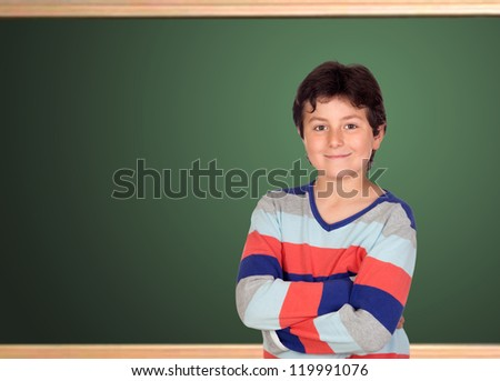 Adorable student at school in front of a blackboard - stock photo