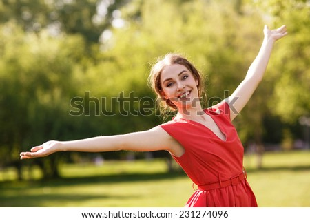 Adorable summer young woman in red dress, carefree dancing enjoying nature - stock photo