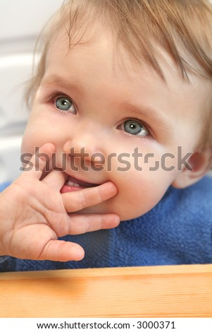 adorable teary eyed baby sucking his / her finger with the little palm of the hand showing - stock photo