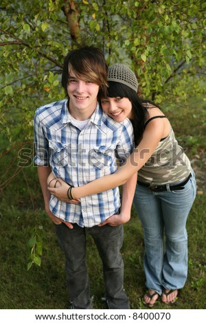 Adorable teen couple hugging outside