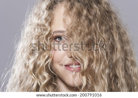 Adorable teenage girl with messy hair smiling - stock photo