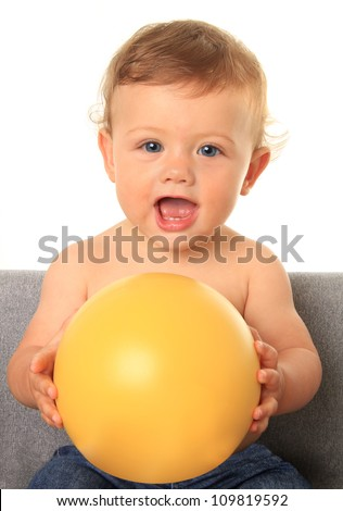 Adorable ten month old baby boy holding a yellow ball. Add your own text onto the ball. - stock photo