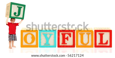 Adorable three year old american boy holding colorful alphabet blocks spelling the word JOYFUL - stock photo