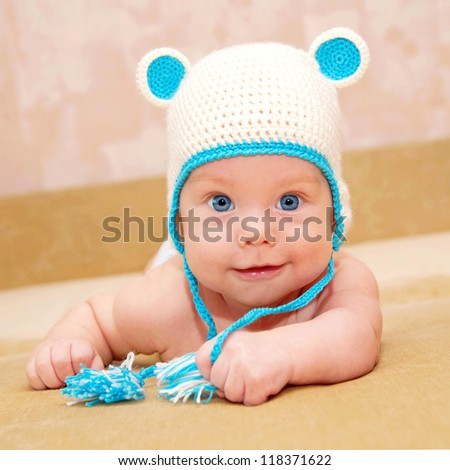 Adorable tiny smiling baby with blue eyes lying on the sofa. Selective focus on the child's face. Kid wearing a funny knit handmade cap with ears - stock photo