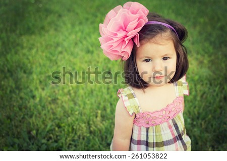 Adorable toddle girl with big pink bow headband and cute romantic pink and green dress smiling looking at camera against green grass background. Horizontal, retouched, filter, copy space. - stock photo