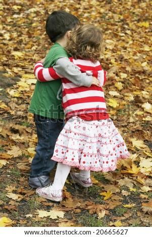 adorable toddler boy and girl hugging - stock photo