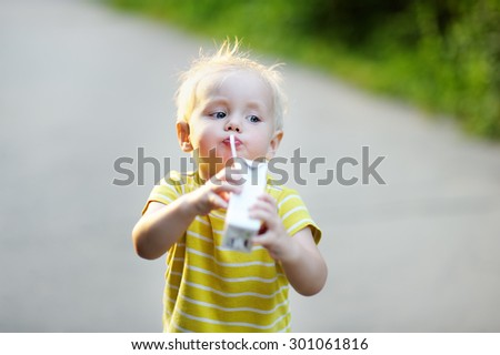 Adorable toddler boy drinking milk or juice outdoors  - stock photo