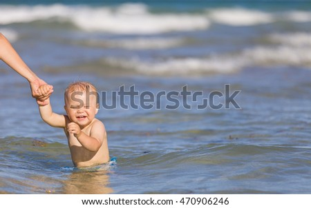 Adorable toddler boy enjoying swimming in the ocean on a sunny day. Mother and child in the sea. Family on vacations. Little baby in water, outdoors.