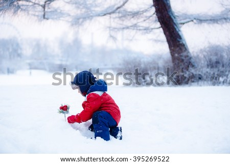 Adorable toddler boy having fun with snow on winter day - stock photo