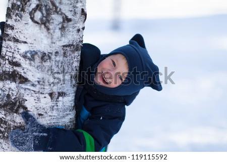 Adorable toddler boy hugging birch tree - stock photo