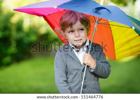Adorable toddler boy of three years with colorful umbrella in a park