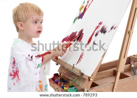 Adorable Toddler Boy Painting at Easel. Shot in studio over white.
