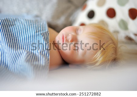 Adorable toddler boy sleeping in a bed - stock photo