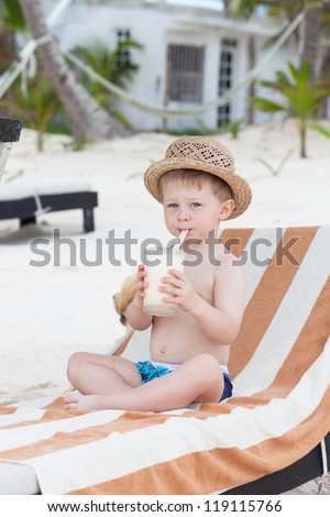 Adorable toddler boy with a glass of milkshake - stock photo