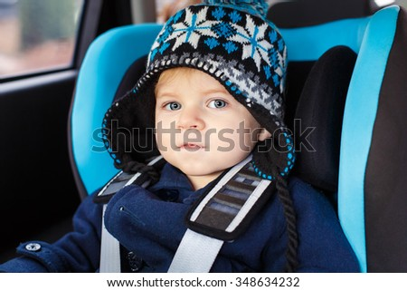 Adorable toddler boy with blue eyes sitting in car seat. child in winter clothes. Safe travel, children safety, transportation concept - stock photo