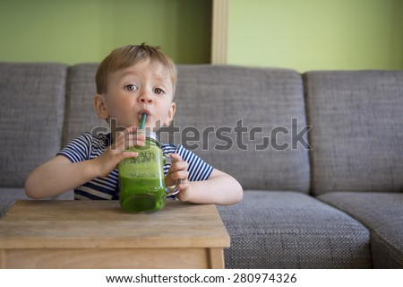 adorable toddler drinking a green smoothie - stock photo