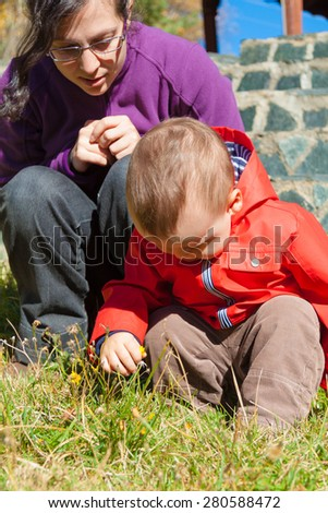 Adorable toddler exploring yellow flower and his mother overseeing him - stock photo