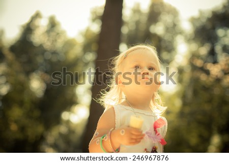 Adorable toddler girl eating an ice cream.  Hippie style. Many friendship bracelets. Unusual coulomb. Shoot from below. Natural light. - stock photo