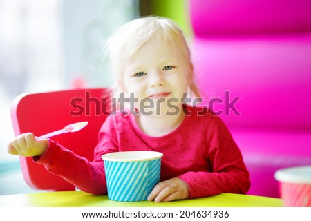 Adorable toddler girl eating ice cream in a colorful outdoor cafe - stock photo
