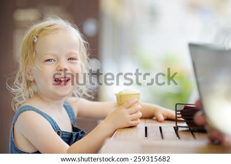Adorable toddler girl eating ice cream in a outdoor cafe  - stock photo