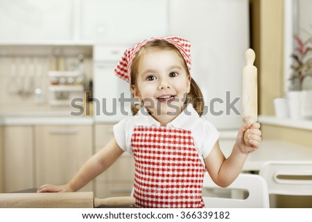 Adorable toddler girl helping at kitchen with baking  - stock photo