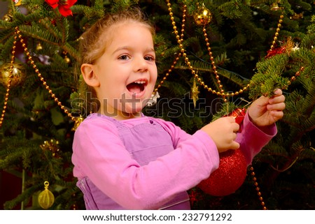 Adorable toddler girl holding decorative toy ball on Christmas tree branch - stock photo