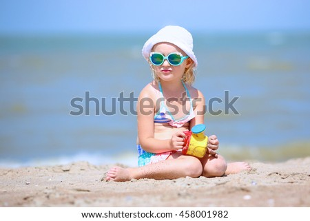 Adorable toddler girl in pretty  swimsuite playing with toys on wide sandy beach - stock photo