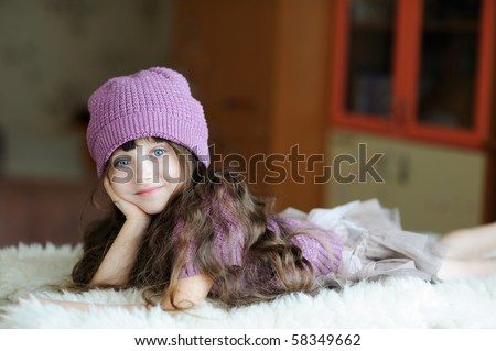 Adorable toddler girl in purple hat is lying on white fur - stock photo