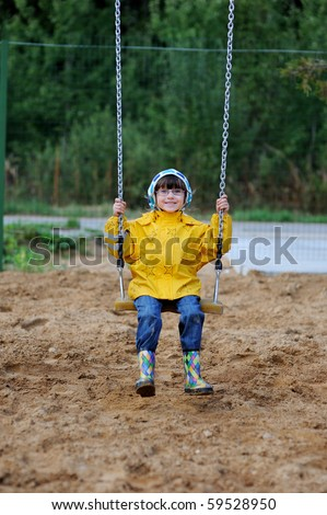 Adorable toddler girl in yellow rain coat and colorful rain boots playing on playground on swing