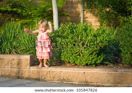 Adorable toddler girl jumping of fencing on a warm summer day - stock photo