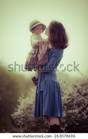 Adorable toddler girl kissing her Mom in the park. Special colors. - stock photo