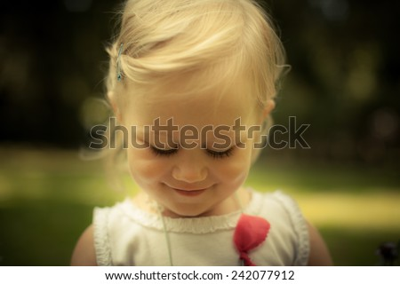 Adorable toddler girl looking down. Soft focus. Eyes closed - stock photo